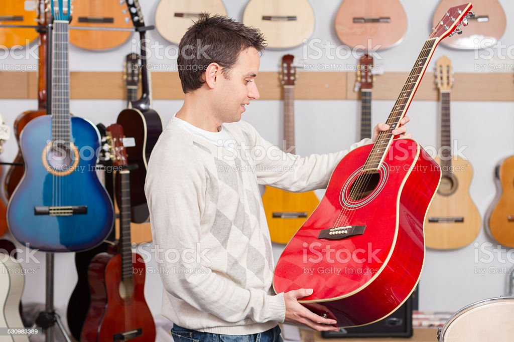 Man looking and holding guitar music shop stock photo