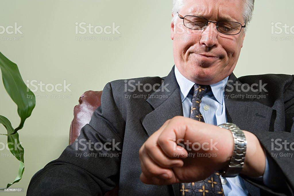 Man looking anxiously at watch stock photo