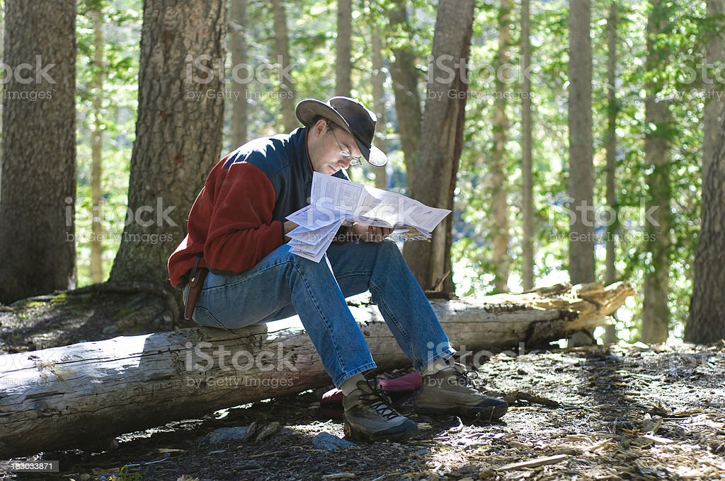 Man looking at a map in the forest royalty-free stock photo