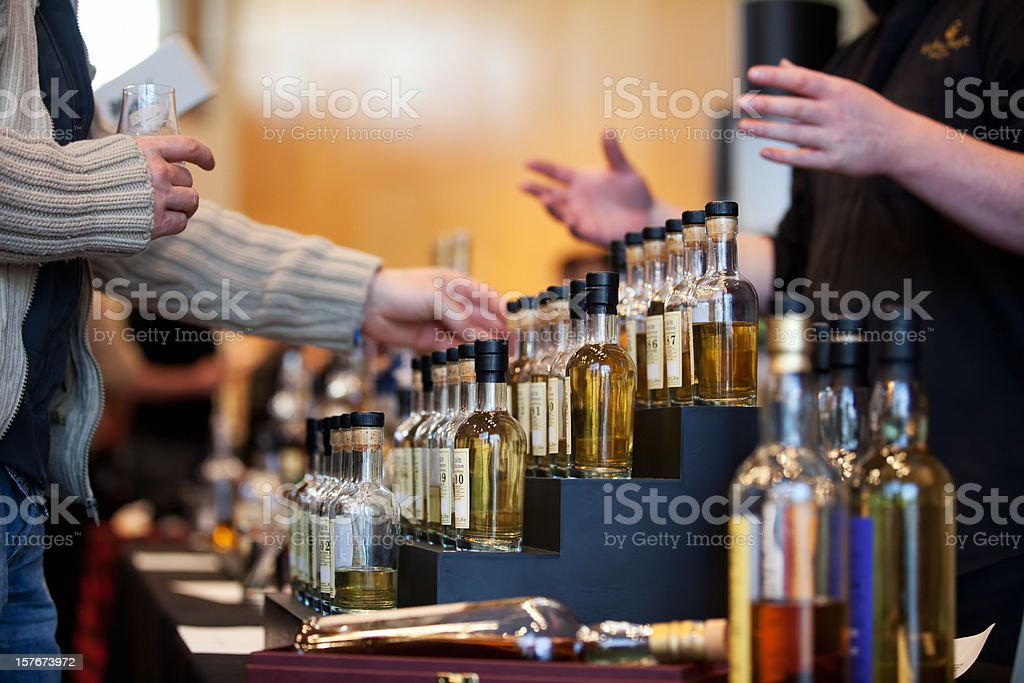 Man looking at a whiskey bottle display stock photo