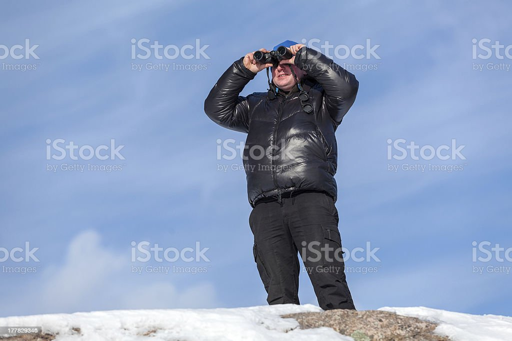 Man looking at binocular on the rock with blue sky royalty-free stock photo