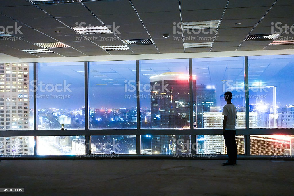 Man looking at cityscape from office window stock photo