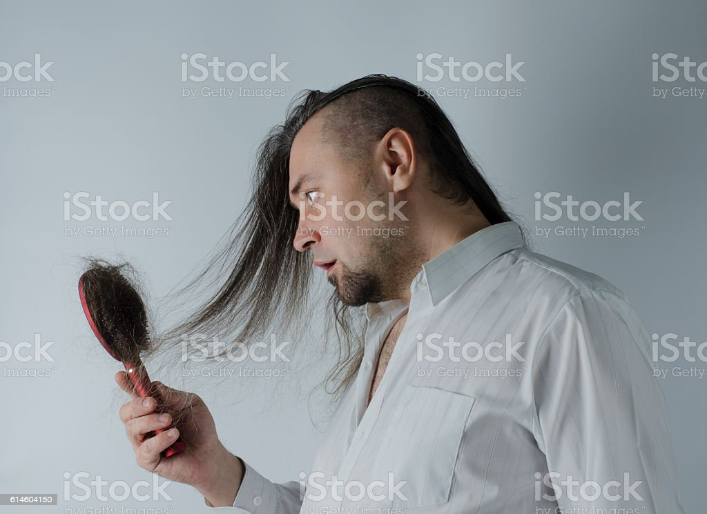 man looking at  hairbrush stock photo