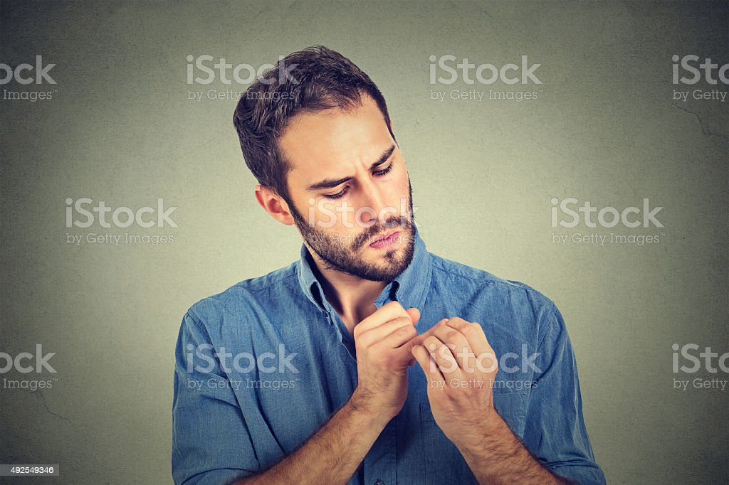 man looking at hands nails obsessing about cleanliness germs stock photo