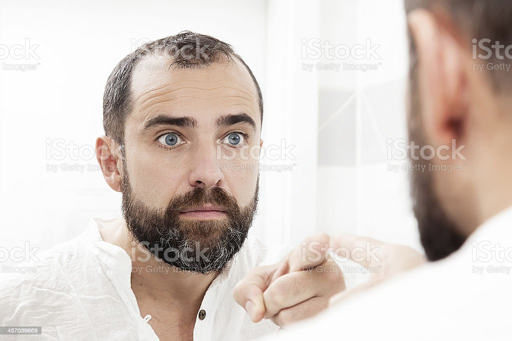 Man looking at himself in the mirror and pointing stock photo