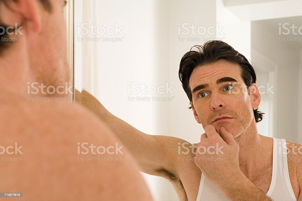 Man looking at himself in the mirror royalty-free stock photo