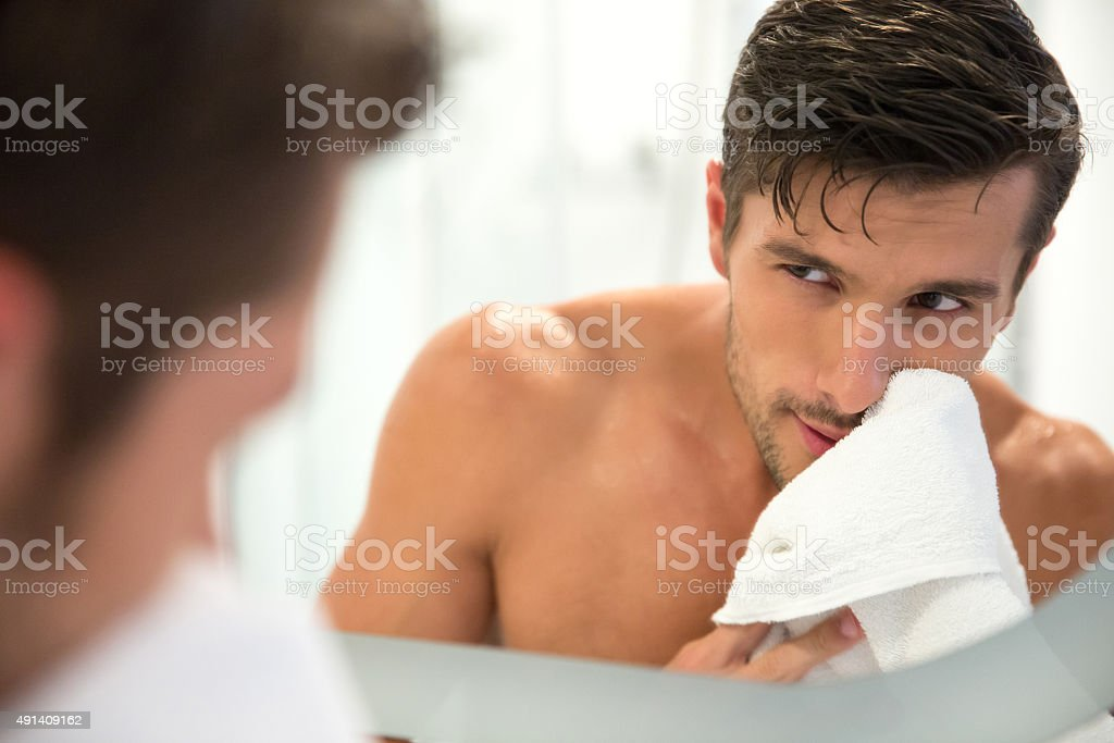 Man looking at his reflection in the mirror stock photo