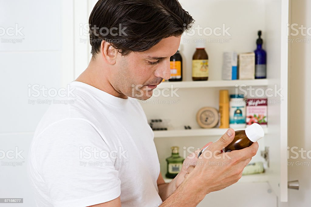 Man looking at label on cough medicine stock photo