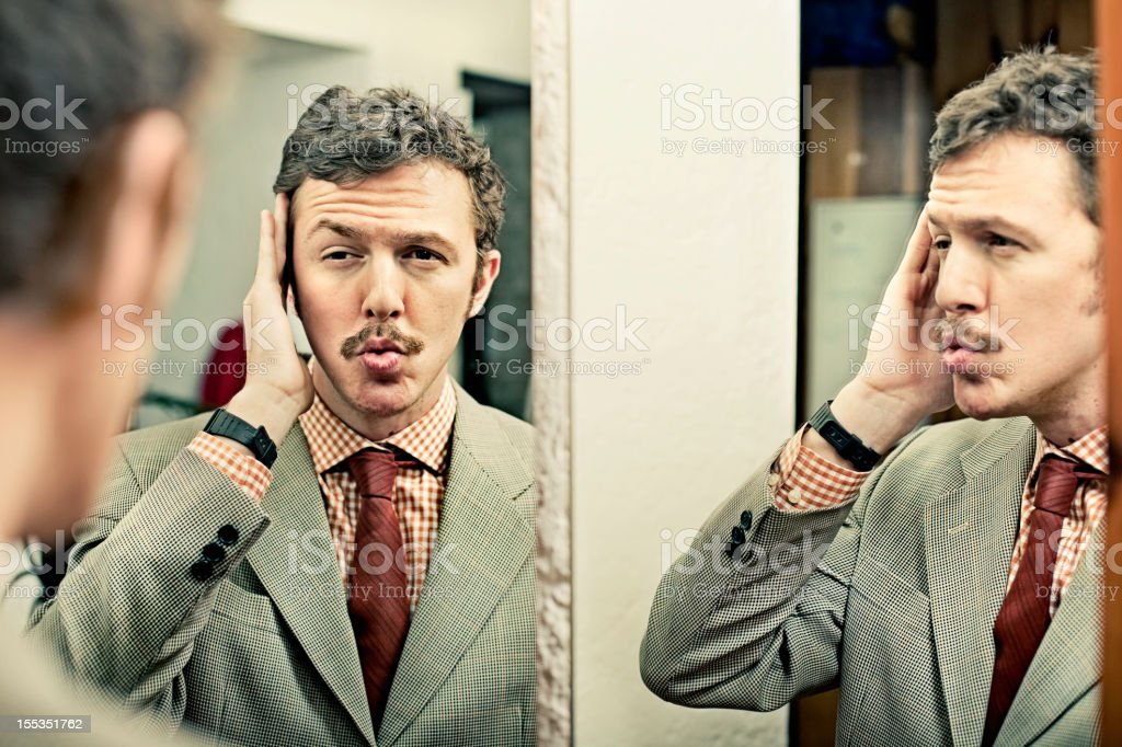 Man looking at reflection in mirror stock photo