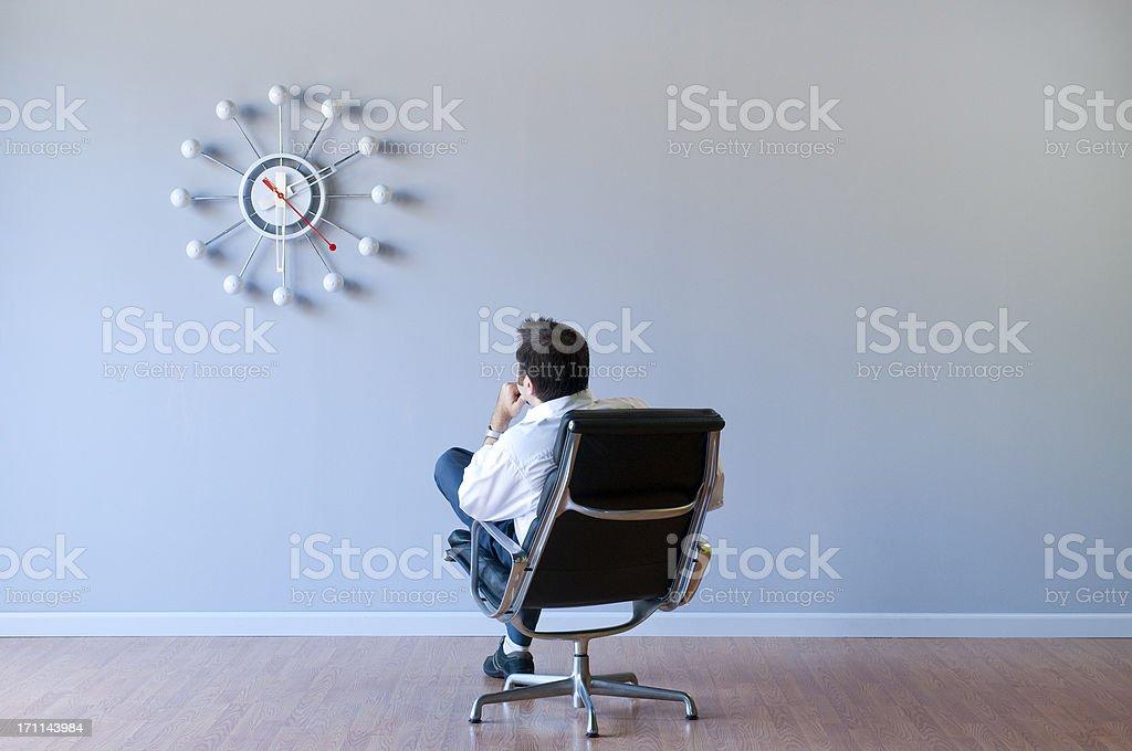 Man Looking At Retro Clock In Empty Room royalty-free stock photo