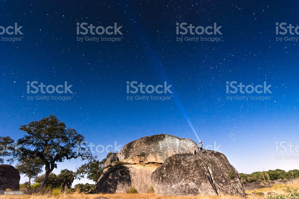 man looking at stars with a flashlight stock photo