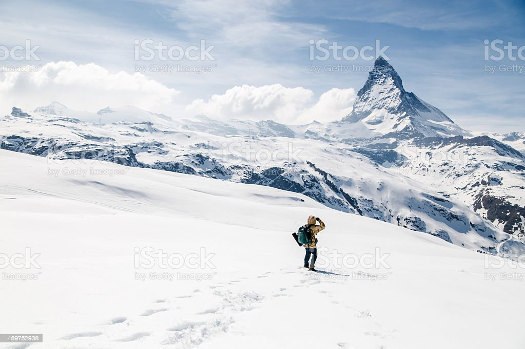 Man looking at the background of Matterhorn. stock photo