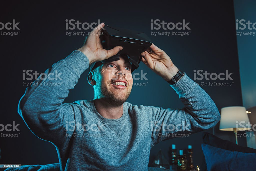Man looking at VR film with virtual reality glasses headset stock photo