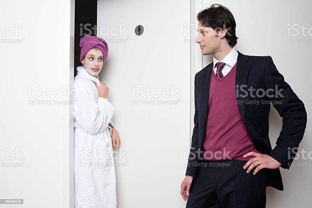 Man looking at woman coming out of bathroom stock photo