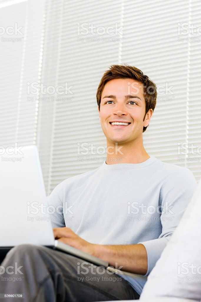 Man Looking Away While Sitting With Laptop In Living Room stock photo