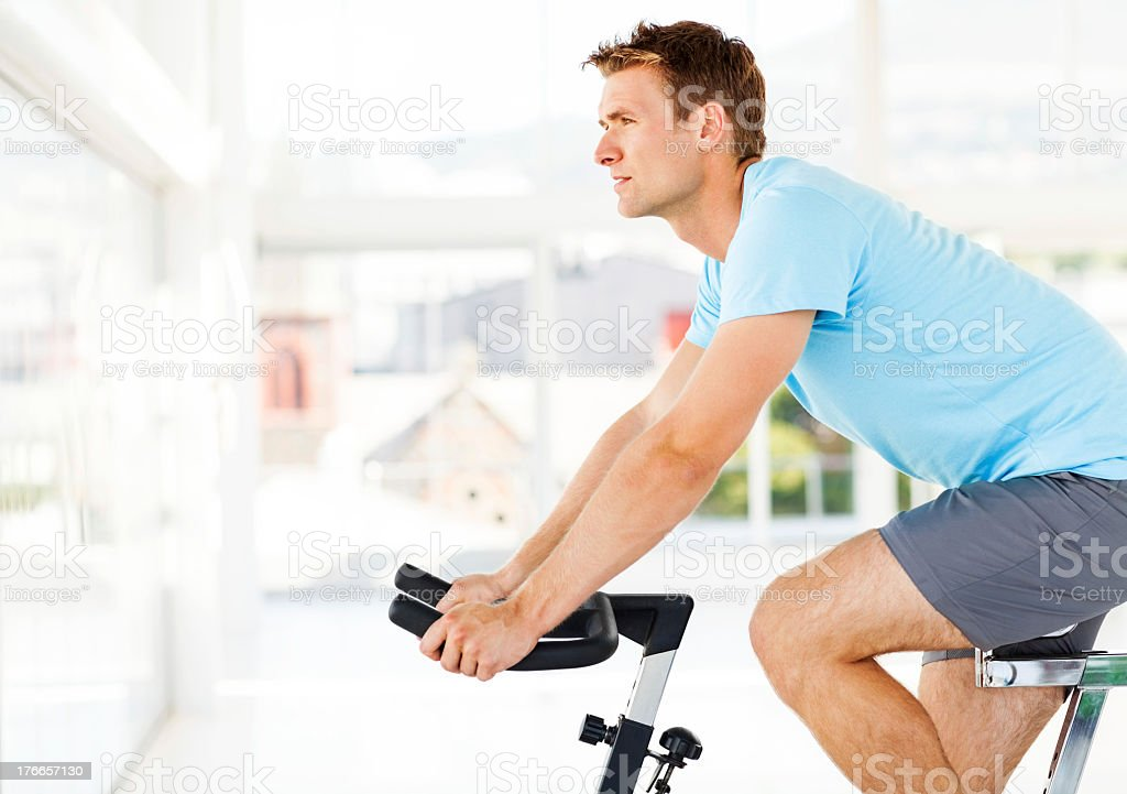 Man Looking Away While Training On Exercise Bike In Club stock photo