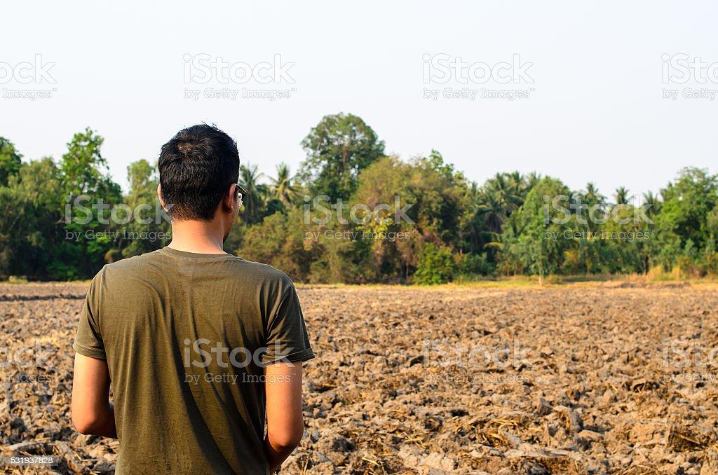 man looking barren ground stock photo