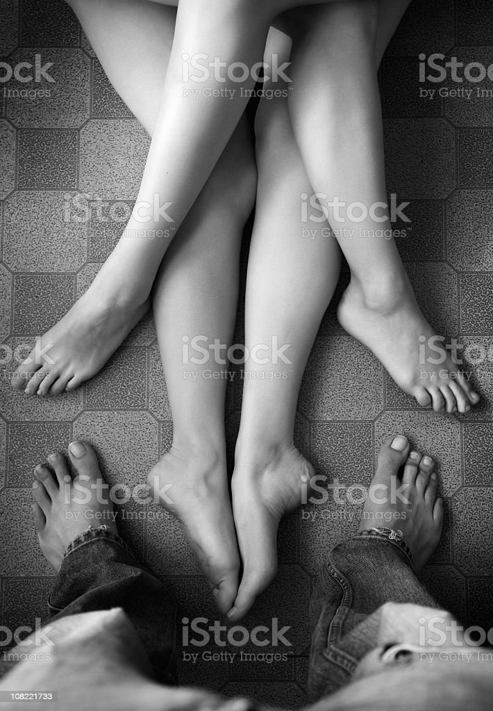 A man looking down at two sets of bare female legs royalty-free stock photo