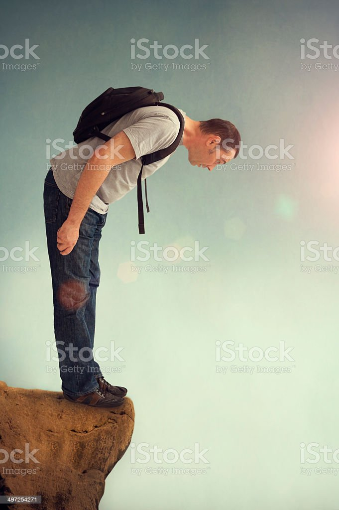 man looking down from a rocky ledge stock photo