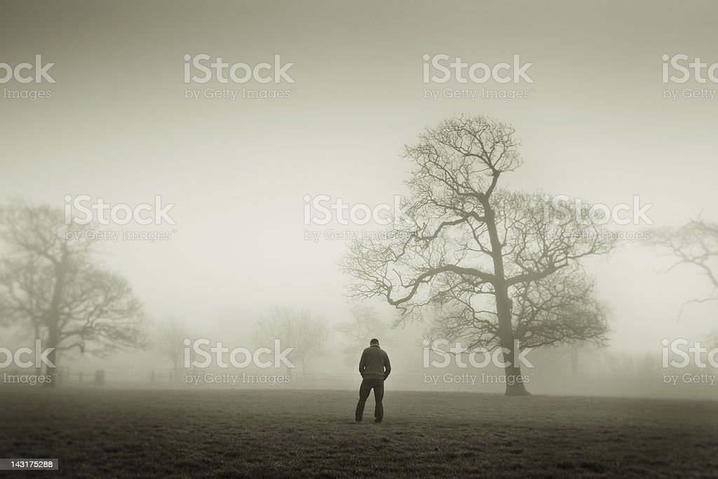 Man looking down in a foggy landscape stock photo