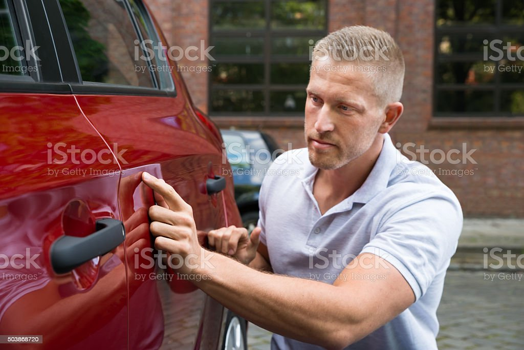 Hombre buscando rasguña en su coche - foto de stock
