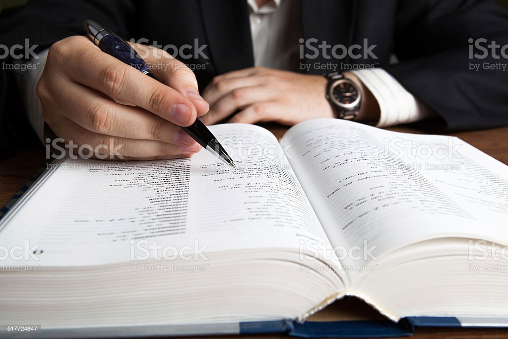 man looking in the large dictionary stock photo