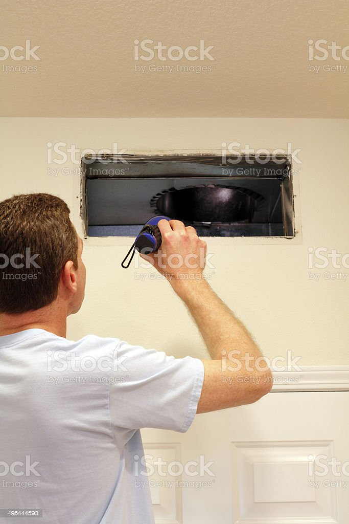 Man Looking into Air Duct stock photo