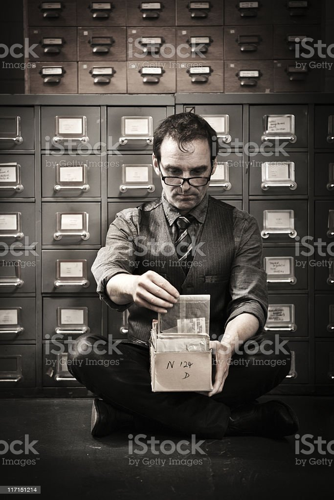Man looking into box for archived photographies royalty-free stock photo