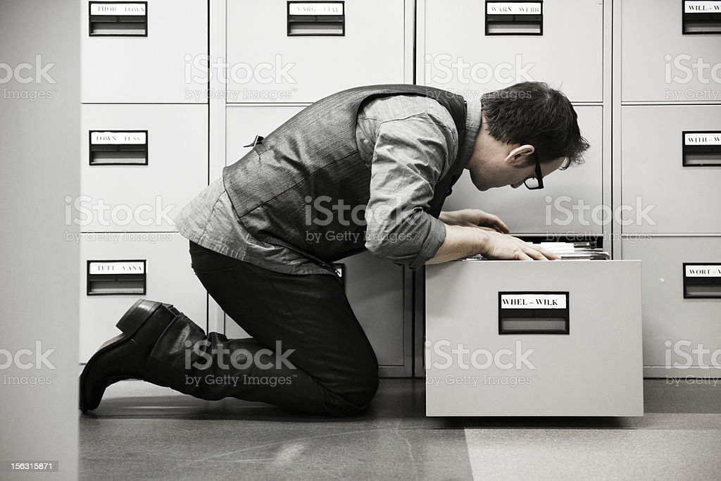 Man looking into filing cabinet stock photo