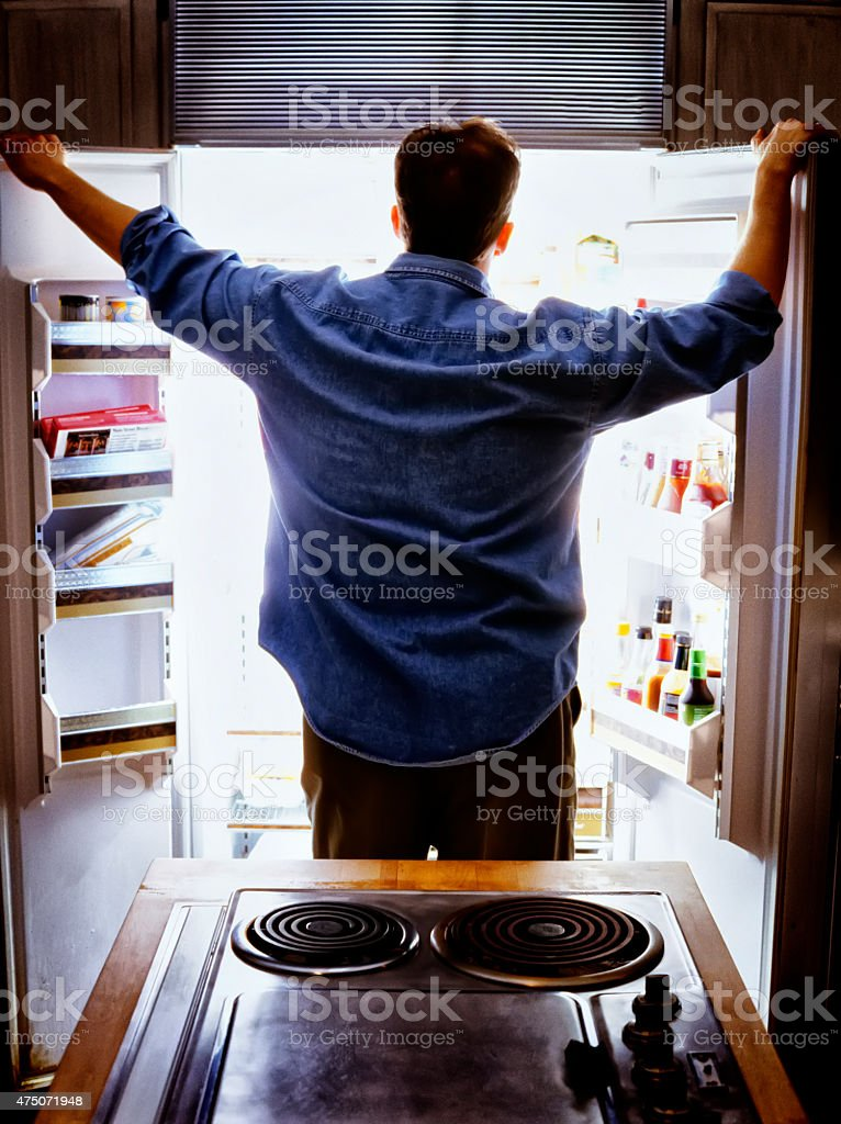 Man looking into refrigerator for food. stock photo
