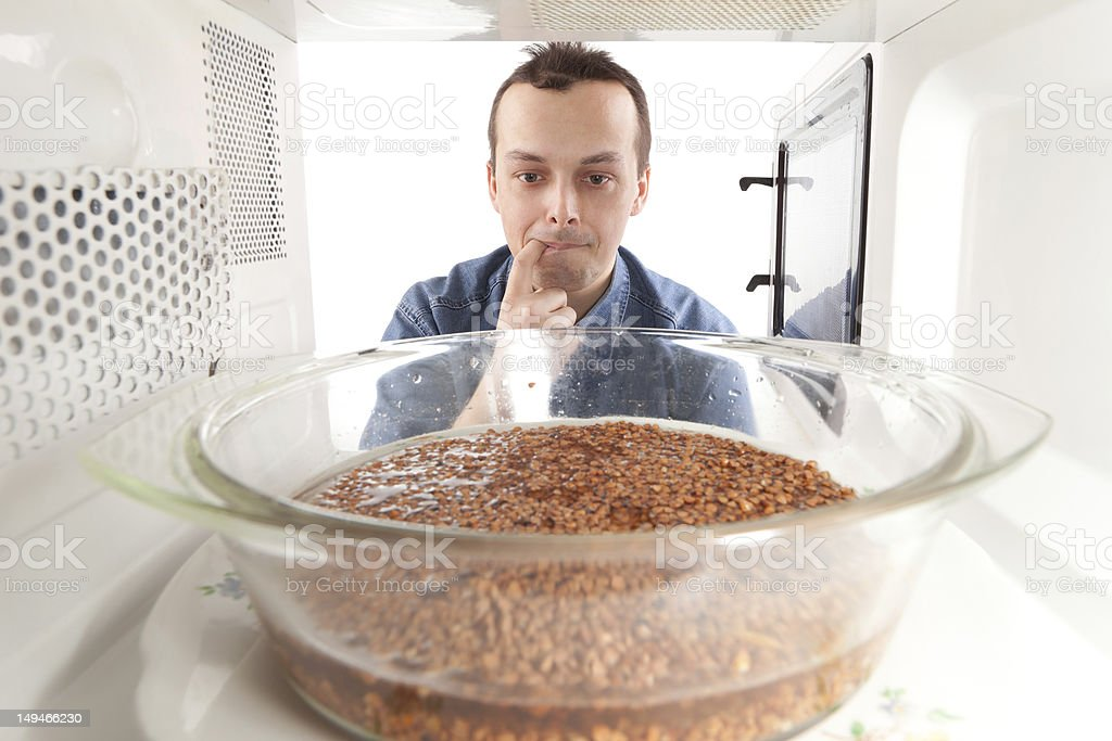 Man looking into the microwave wondering how to cook stock photo