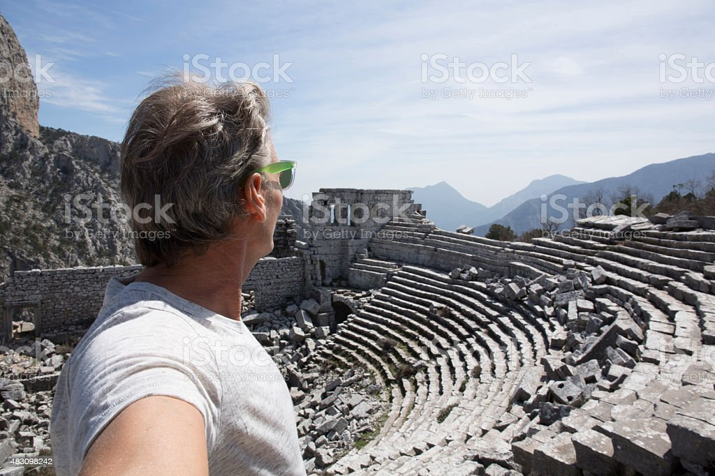 Man looking out above theatre, ancient Greek ruin stock photo