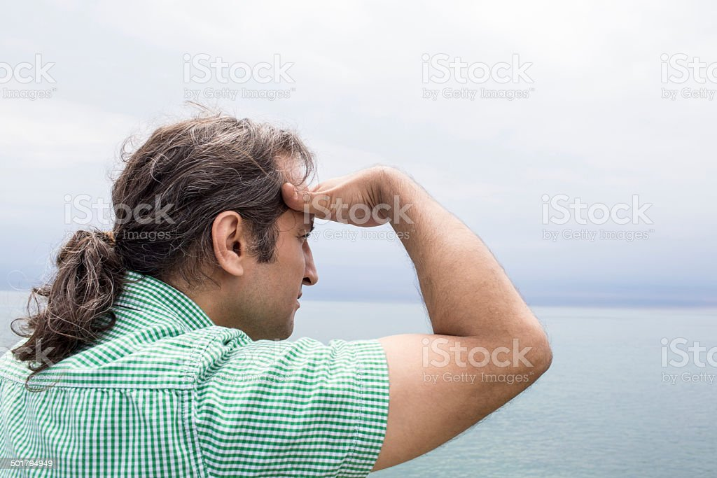 Man looking out into the horizon over water royalty-free stock photo