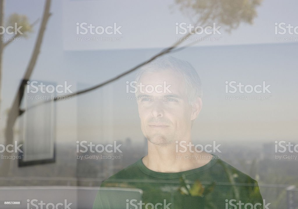 Man looking out living room window stock photo