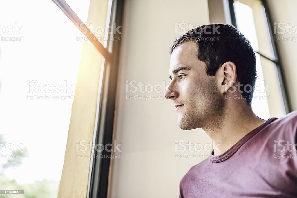 Man looking out of the Window stock photo
