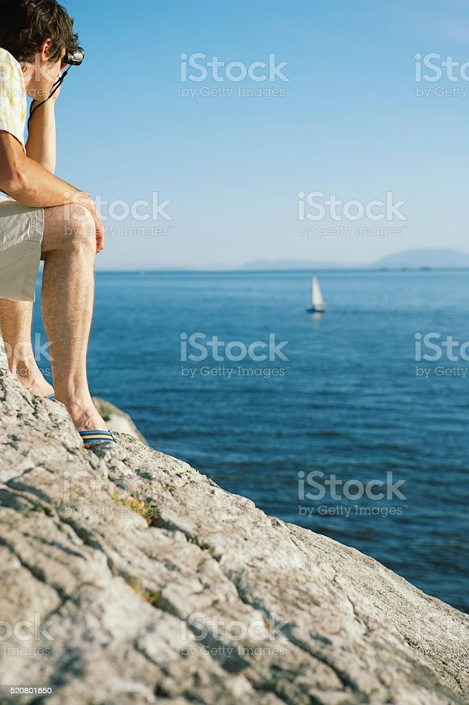 Man looking out over the ocean stock photo