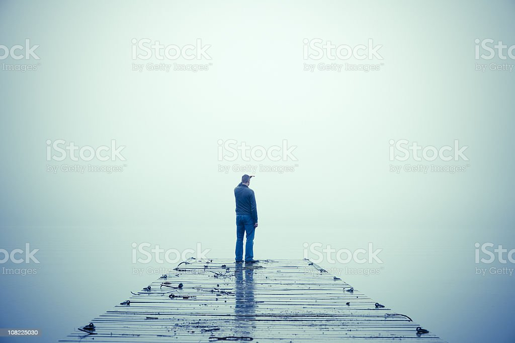 Man Looking Out Through Fog and Standing on Dock stock photo