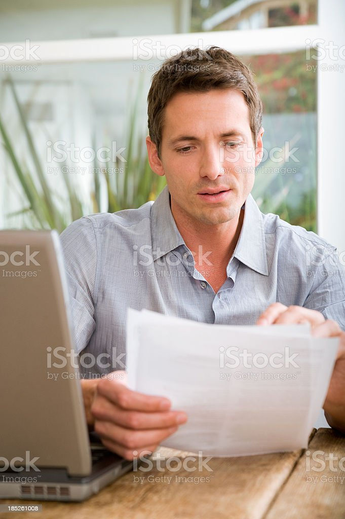 A man looking over his papers with his laptop royalty-free stock photo