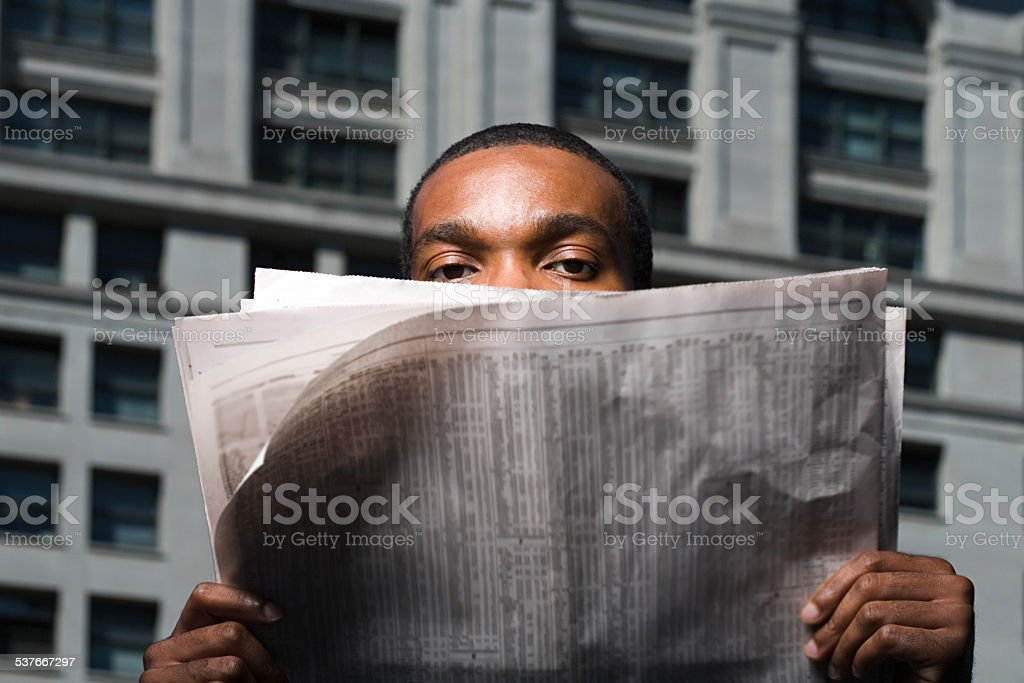 Man looking over newspaper stock photo