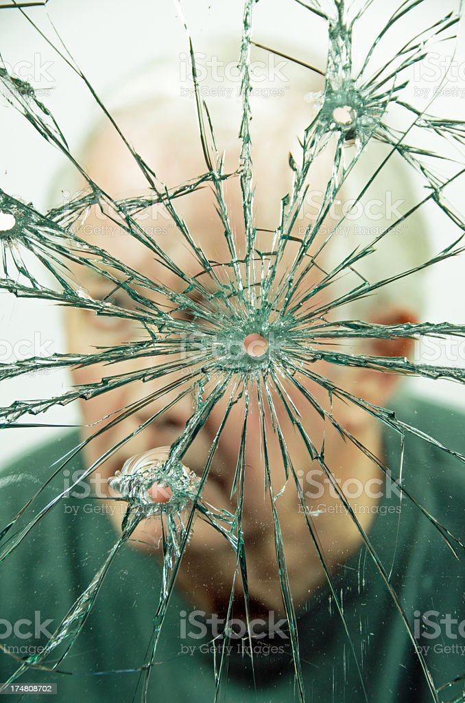Man looking through a bullet hole in shattered glass. royalty-free stock photo