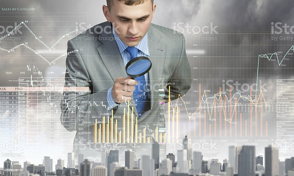 A man looking through a magnifying glass at a graph stock photo