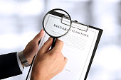 man looking through a magnifying glass.  Blank insurance claim form