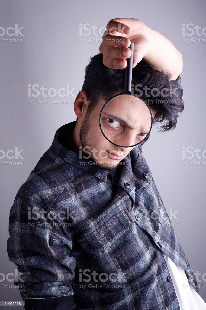 Man looking through a magnifying glass stock photo