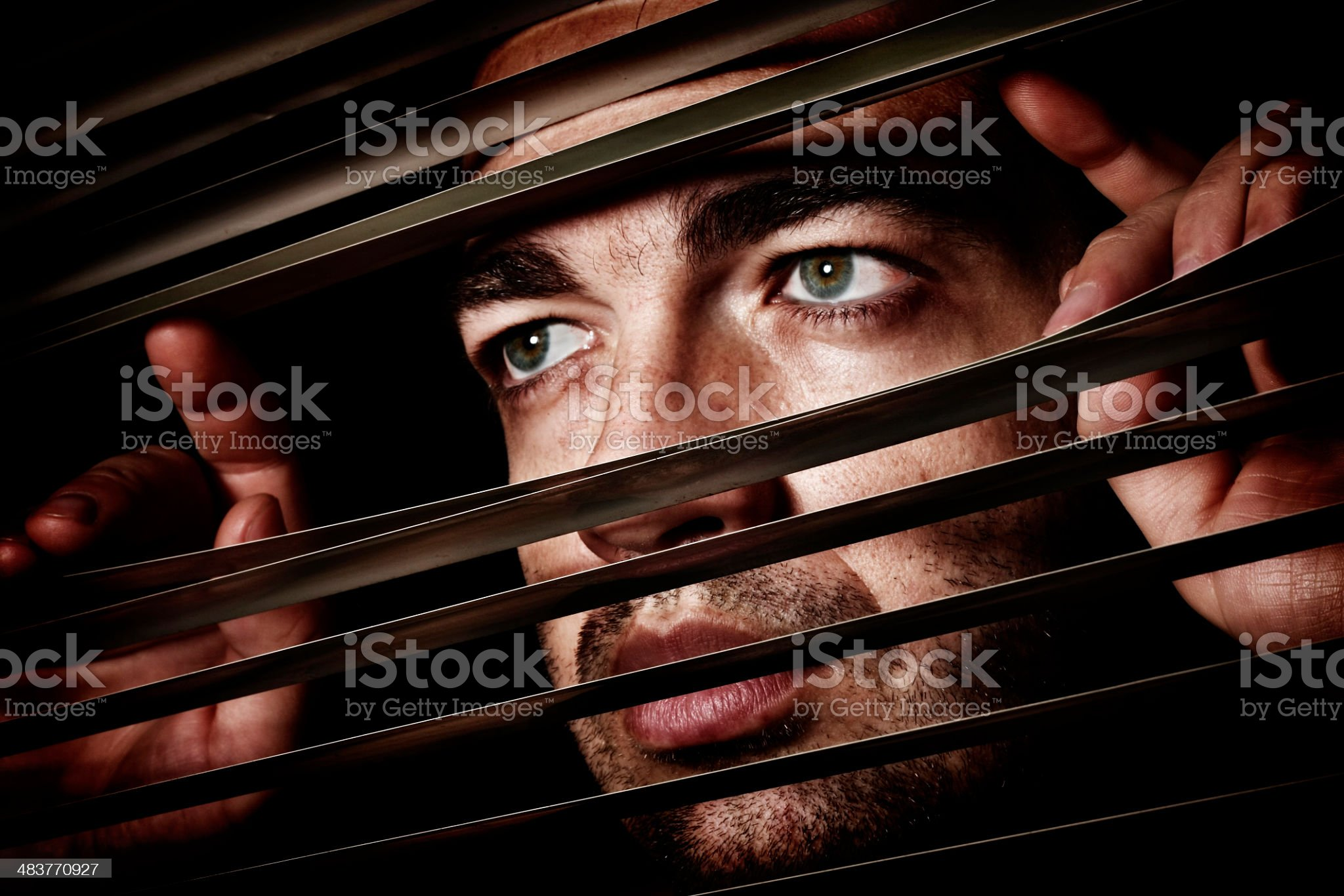 Man looking through blinds royalty-free stock photo