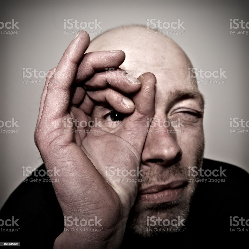 Man Looking Through Hole Made with Fingers royalty-free stock photo