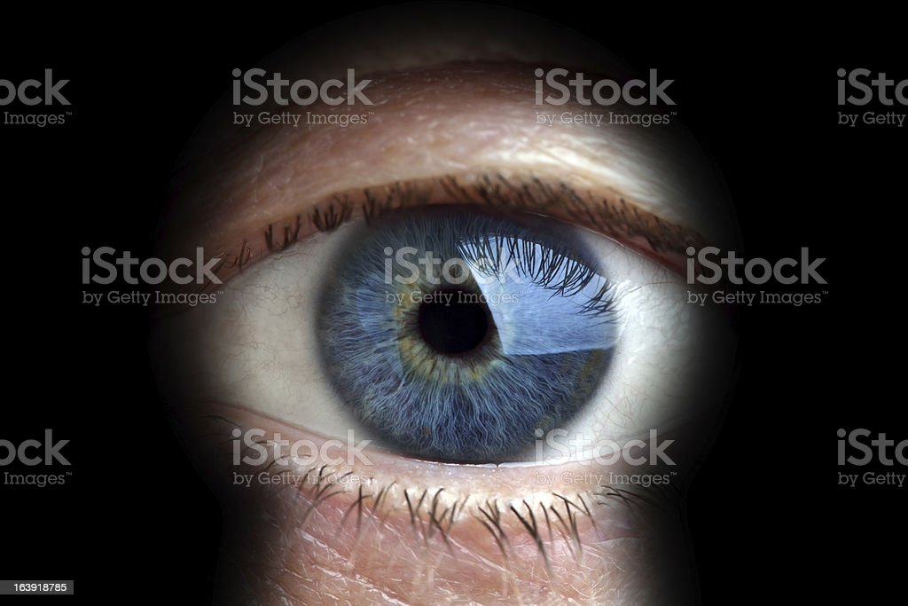 Man looking through keyhole stock photo