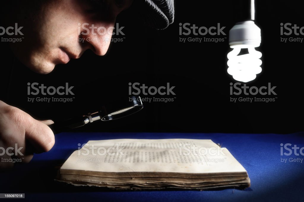 Man looking to an old book through magnifying glass stock photo