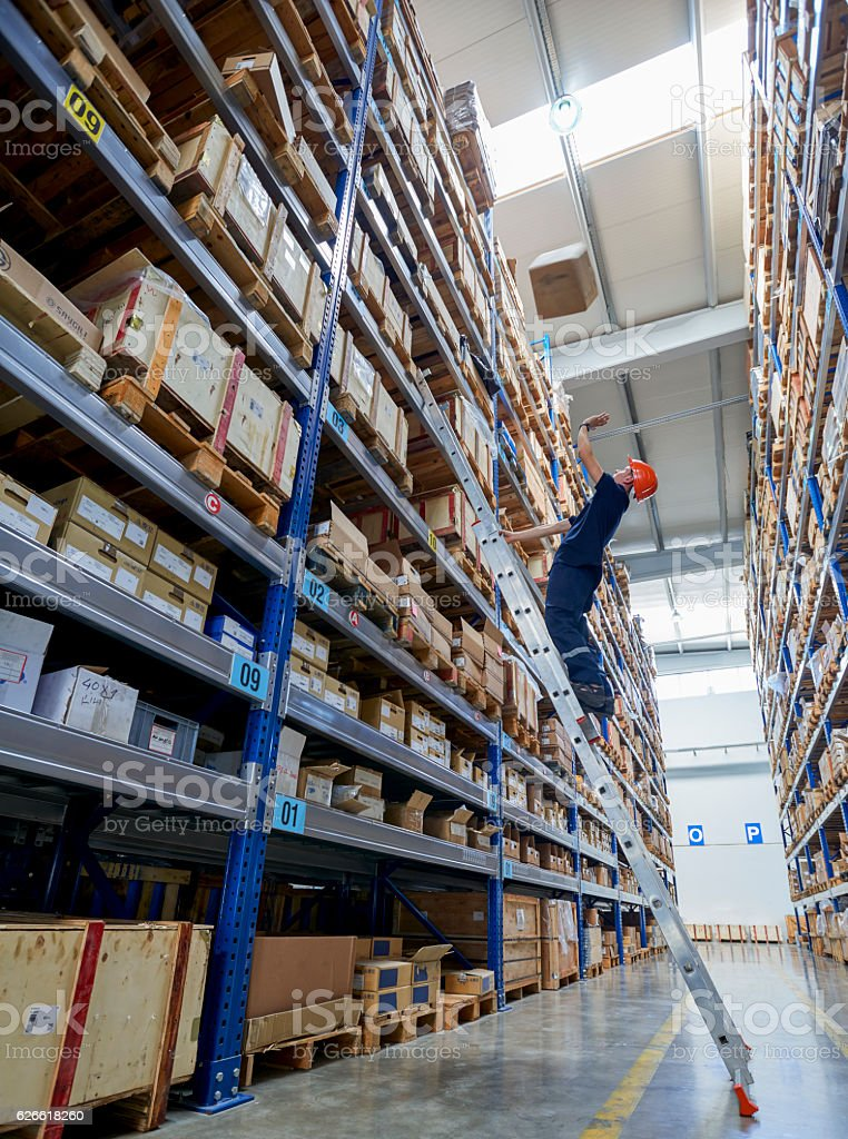 Man looking up at box falling on him, warehouse stock photo