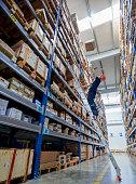 Man looking up at box falling on him, warehouse