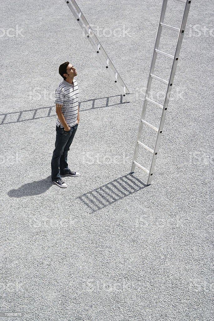 Man looking up at ladder outdoors royalty-free stock photo